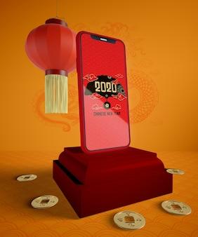 Maqueta de teléfono con monedas de oro para el año nuevo chino