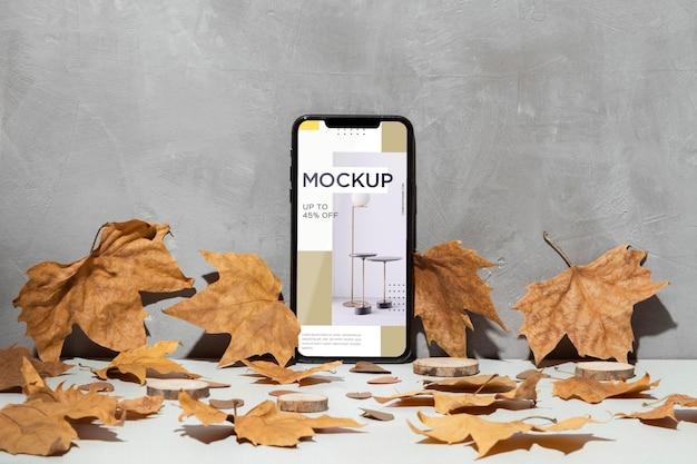 Maqueta de teléfono móvil apoyado en la pared rodeada de hojas