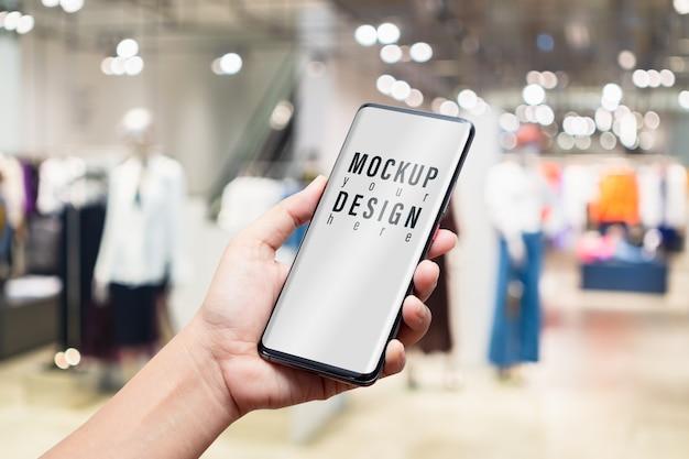 Maqueta de teléfono móvil en la tienda de ropa de mujer de moda.