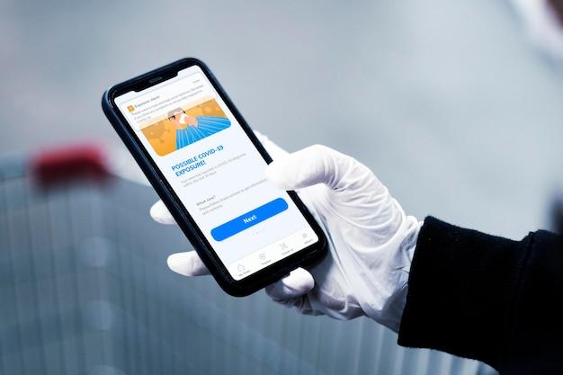 Maqueta de teléfono con persona con guantes y sosteniendo el dispositivo