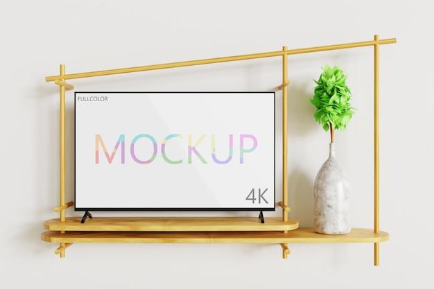 Maqueta de televisión a todo color en el escritorio de pared de madera