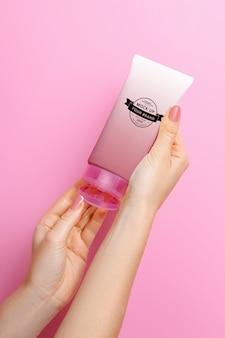 Maqueta de tubo de crema en manos en un espacio rosa