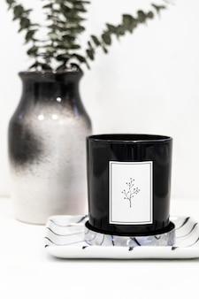 Maqueta de vela negra por un jarrón