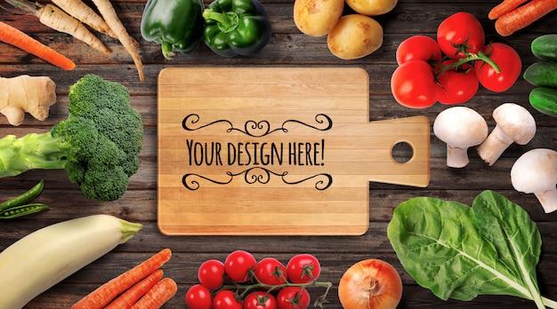 Maqueta de verduras crudas frescas y tabla de cortar de madera