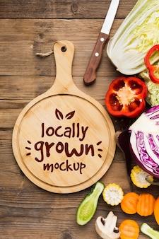 Maqueta de verduras cultivadas localmente y tabla de cortar