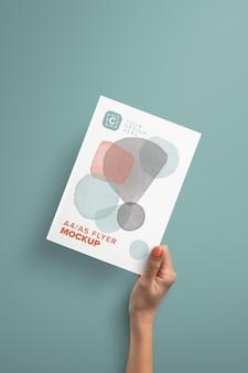 Maqueta vertical de mano sujetando papel a4a5 en diagonal