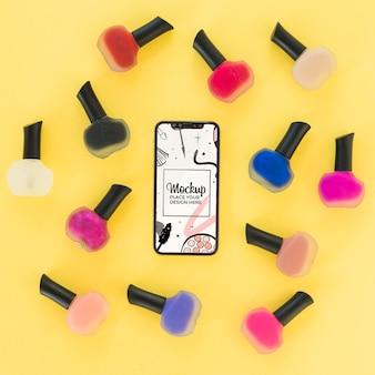 Maqueta de vista superior con esmalte de uñas y teléfono móvil