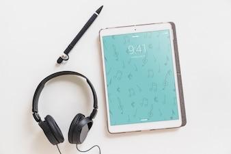 Maquete de música com fones de ouvido ao lado do tablet