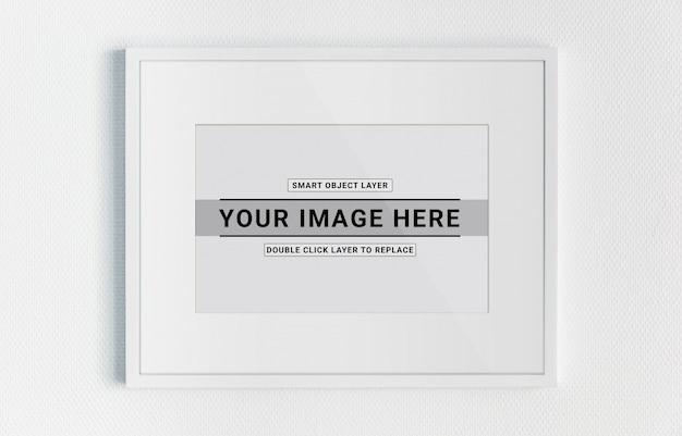 Marco blanco colgado en una maqueta de pared blanca