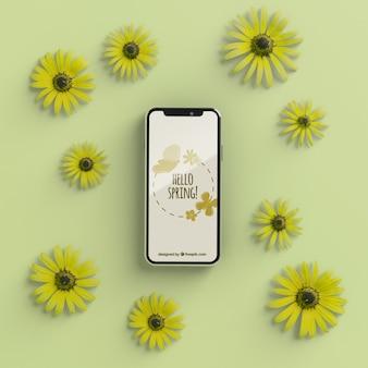 Marco floral con maqueta de dispositivo móvil