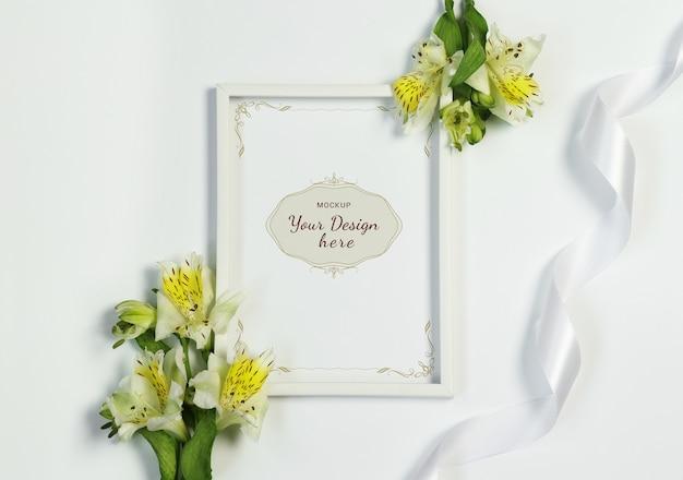 Marco de la foto de la maqueta con las flores y la cinta en el fondo blanco