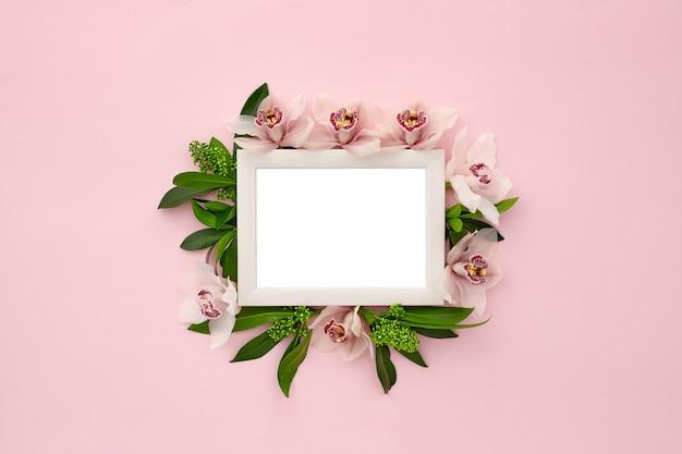 Marco de fotos decorado con hojas verdes y flores de orquídeas