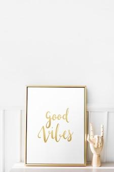 Marco de fotos dorado por el maniquí de mano sobre una mesa blanca