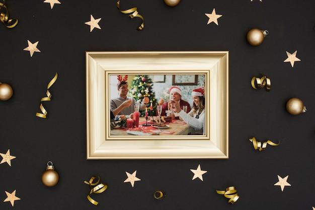 Marco de fotos familiar con bolas colgantes doradas y estrellas