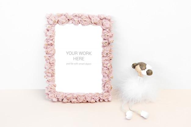 Marco de fotos de maqueta con flor rosa rosa y estatuilla
