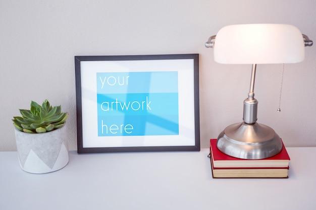 Marco de imagen, libros, lámpara de mesa y planta en maceta en la mesa