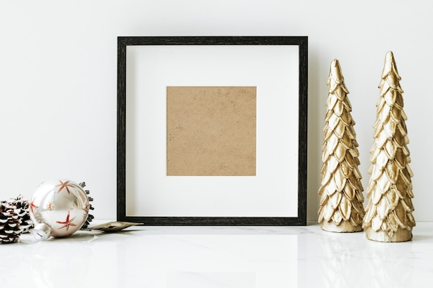 Marco de imagen en una mesa con árbol de navidad dorado