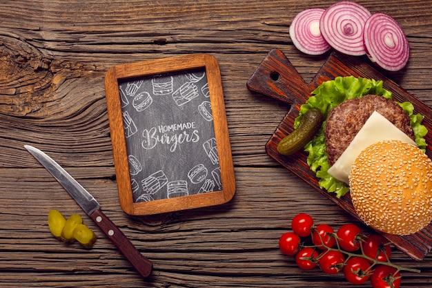 Marco de pizarra de maqueta con hamburguesa sobre fondo de madera