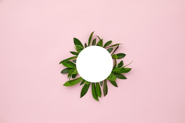 Marco redondo blanco decorado con hojas verdes