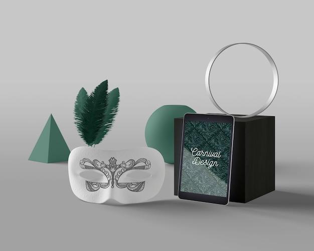 Máscara al lado de la tableta con tema de carnaval