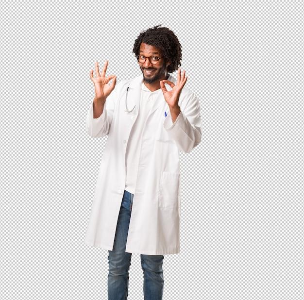 Medico afroamericano bello allegro e sicuro che fa gesto giusto, eccitato e che grida, concetto di approvazione e successo