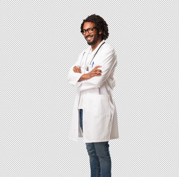 Medico afroamericano bello che attraversa le sue armi, sorridenti e felici