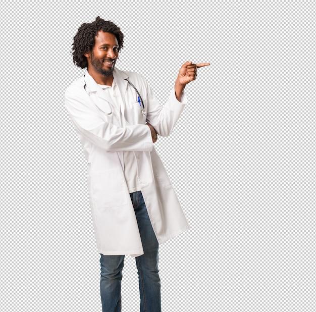 Medico afroamericano bello che indica il lato, sorridendo sorpreso presentando qualcosa, naturale e casuale