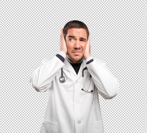Medico interessato che copre le sue orecchie contro fondo bianco