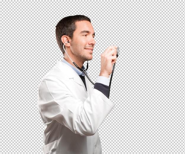 Medico sicuro che per mezzo di uno stetoscopio contro fondo bianco