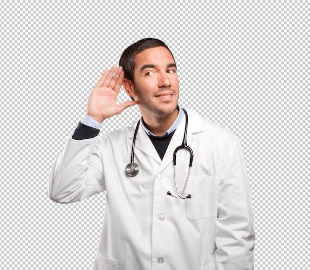 Medico sorpreso con ascolto gesto contro sfondo bianco