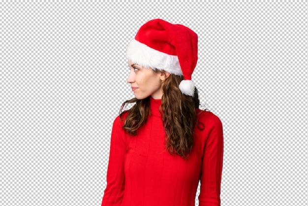 Meisje dat met kerstmishoed aan de kant kijkt