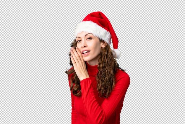 Meisje dat met kerstmishoed iets fluistert