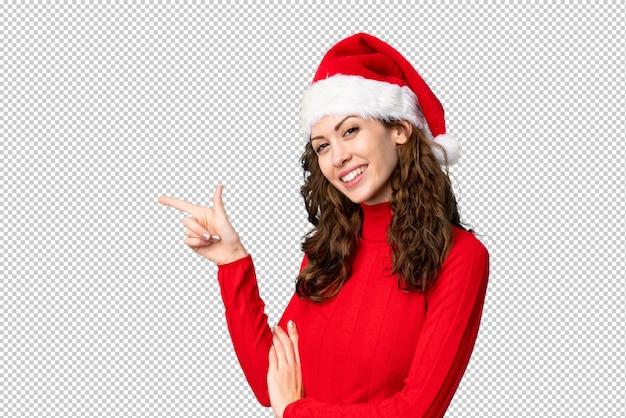 Meisje dat met kerstmishoed vinger aan de kant richt