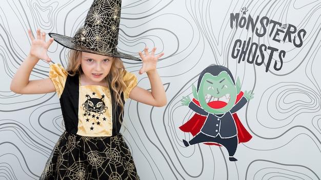 Meisje die een enge gebaar en een vampier met kaap maken