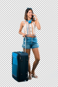 Meisje die met haar koffer reizen die een gesprek met de mobiele telefoon met iemand houden