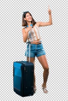 Meisje die met haar koffer reizen die met de wijsvinger richten een groot idee en omhoog kijken