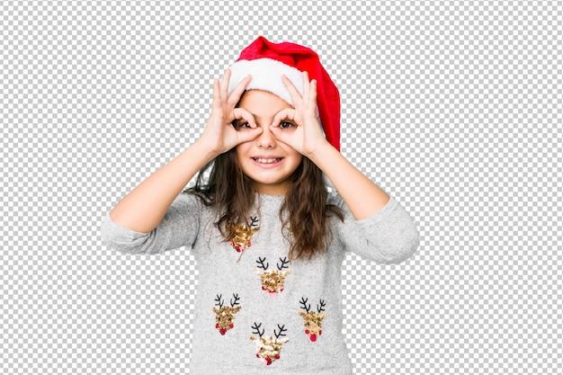 Meisje het vieren kerstmisdag die ok teken over ogen tonen