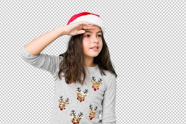 Meisje het vieren kerstmisdag die ver weg houdend hand op voorhoofd kijken.