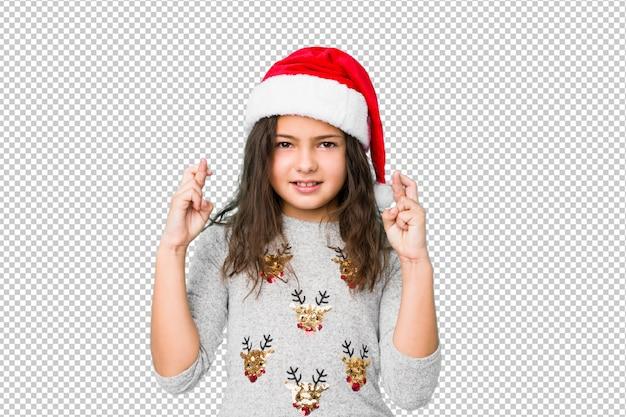 Meisje het vieren kerstmisdag die vingers kruisen voor het hebben van geluk