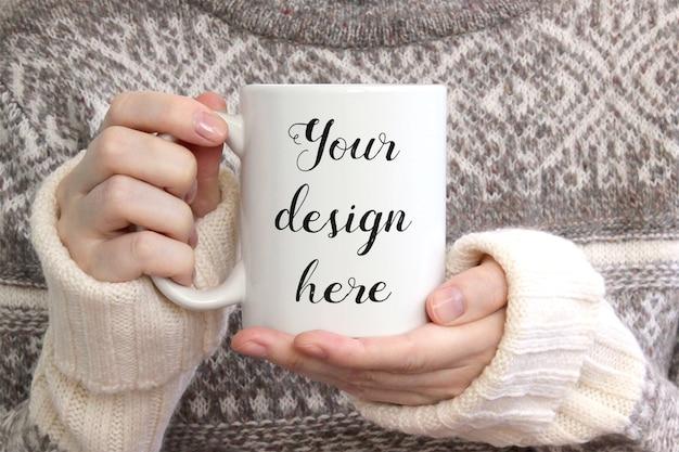 Meisje in gezellige trui houdt witte keramische koffiemok, mock-up