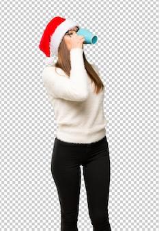 Meisje met het vieren van de kerstvakantie drinken warme koffie in afhaalmaaltijden papier beker