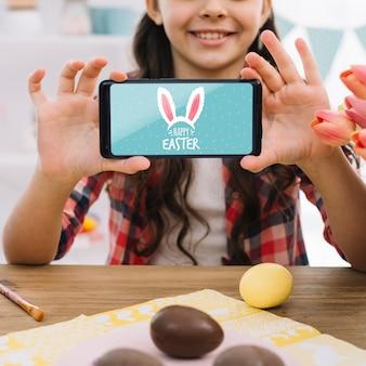 Meisje met smartphonemodel op pasen-dag