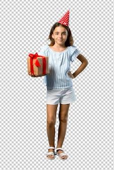 Meisje op een verjaardagsfeestje met een geschenk poseren met armen op heup