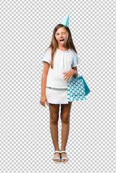 Meisje op een verjaardagsfeestje met een geschenk tas met tong naar de camera met grappige blik