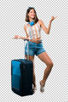 Meisje reist met haar koffer geniet van dansen tijdens het luisteren naar muziek op een feestje