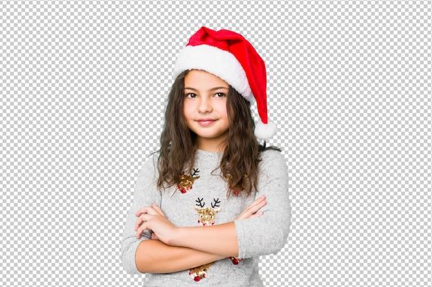 Meisje viert kerstdag die zich zelfverzekerd voelt, gekruiste armen met vastberadenheid.