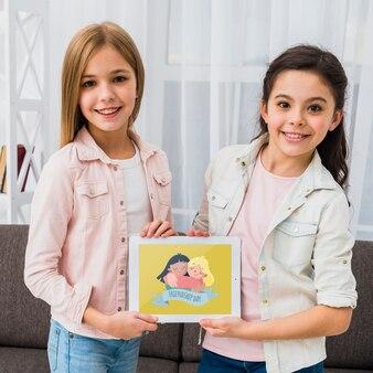 Mejores amigos sosteniendo una tableta juntos maqueta