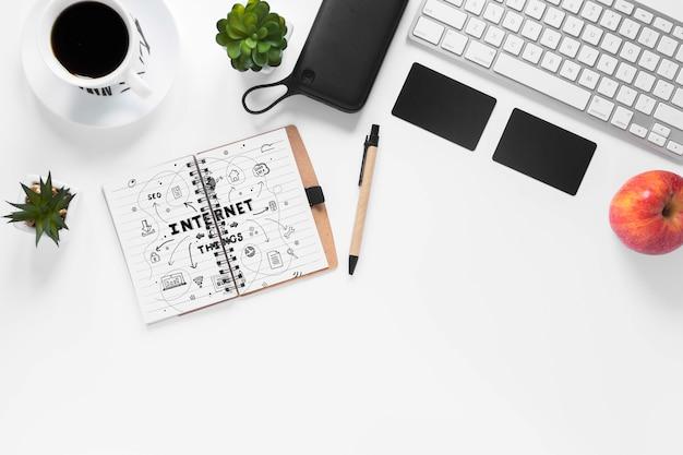 Mela e tastiera del caffè con il taccuino sul modello dello scrittorio