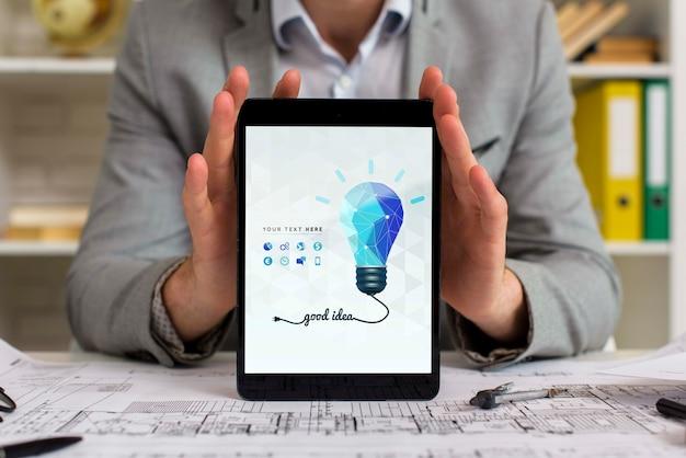 Mens die bij zijn bureau digitale tablet houdt
