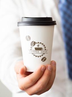 Mens die een kop van koffieclose-up houdt